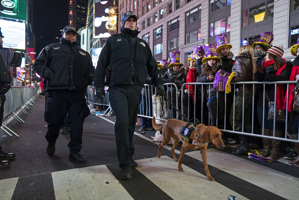 New York police officers walk among revelers who have gathered on Times Square in New York, Saturday, Dec. 31, 2016, to take part in a ...