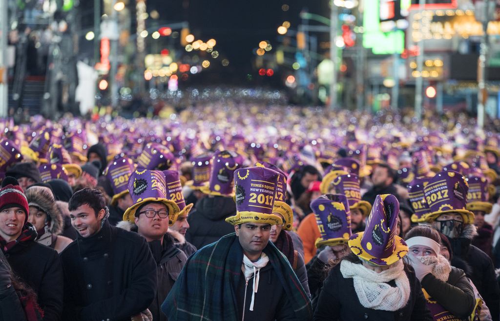 Revelers gather on Times Square in New York Saturday, Dec. 31, 2016, as they take part in a New Year's Eve celebration. (AP Photo/Craig...