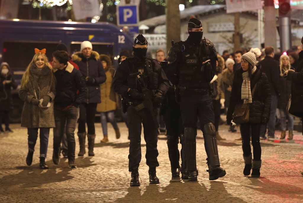 French police officers patrol the Champs Elysees, during the New Year celebrations in Paris, France, Sunday, Jan. 1, 2017. (AP Photo/Ch...