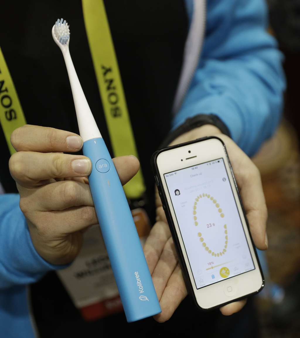 An employee holds up the Ara smart tooth brush at the Kolibree booth during CES Unveiled before CES International, Tuesday, Jan. 3, 201...