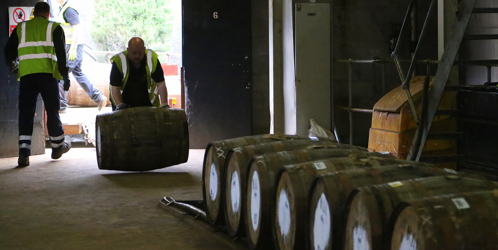 In this photo taken June 30, 2016, a worker rolls in a barrel of whisky at The Macallan distillery in Craigellachie, Scotland. The dist...
