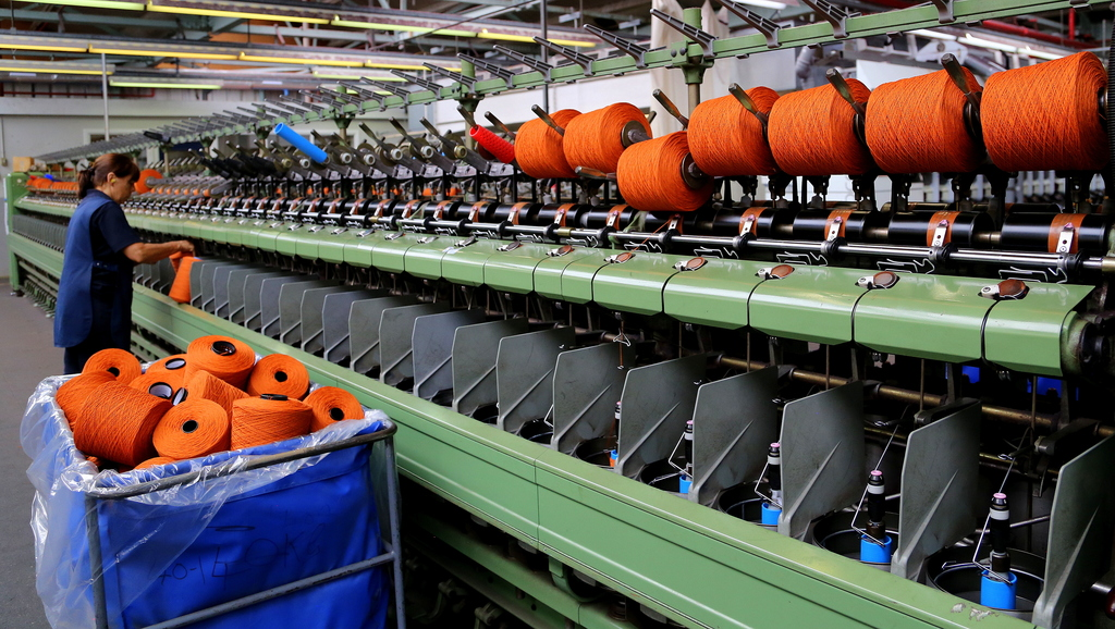 In this photo taken June 29, 2016, bright orange yarn is set up on a machine at the Johnsons of Elgin wool mill in Elgin, in the Speysi...
