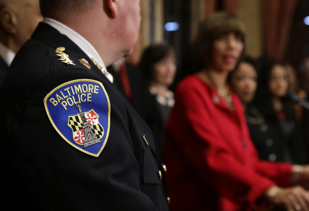The Baltimore Police Department seal is seen on Commissioner Kevin Davis' uniform as he listens to Baltimore Mayor Catherine Pugh durin...