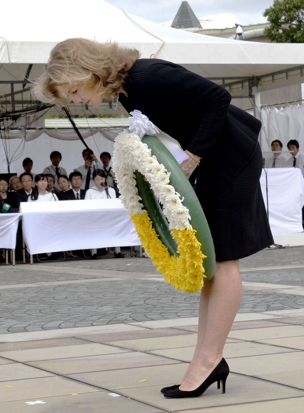 FILE - In this Aug. 9, 2014, file photo, U.S. Ambassador to Japan Caroline Kennedy greets attendants as she offers flowers to the atomi...