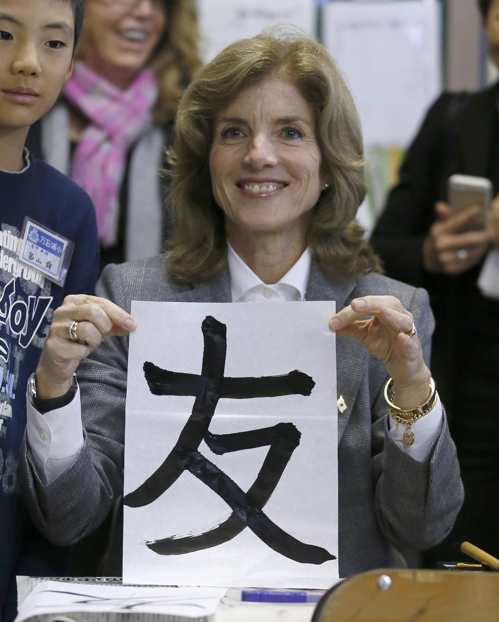 """FILE - In this Nov. 25, 2013, file photo, new U.S. Ambassador to Japan Caroline Kennedy shows her work of the Japanese word of """"friends..."""