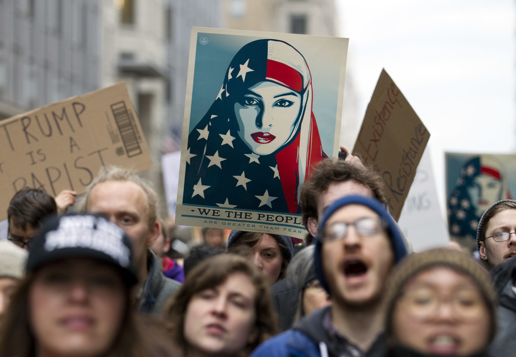 Demonstrators march on the street near a security checkpoint inaugural entrance, Friday, Jan. 20, 2017 in Washington, ahead of Presiden...