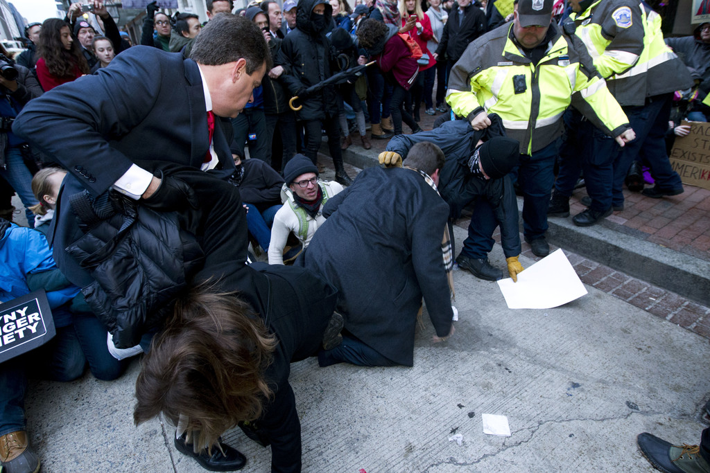 Inaugural attendees move through demonstrators attempting to block people entering a security checkpoint, Friday, Jan. 20, 2017, ahead ...