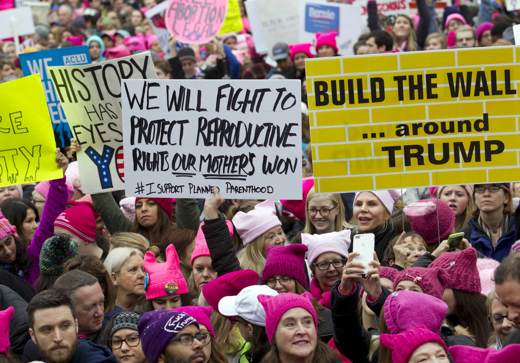 Women with bright pink hats and signs begin to gather early and are set to make their voices heard on the first full day of Donald Trum...