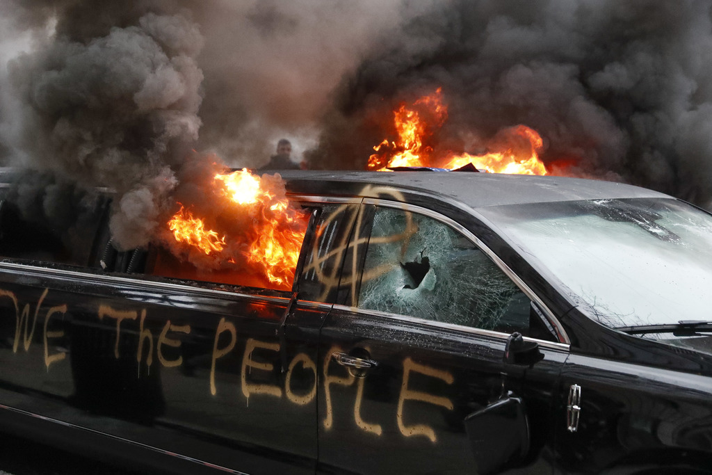 A parked limousine burns during a demonstration after the inauguration of President Donald Trump, Friday, Jan. 20, 2017, in Washington....
