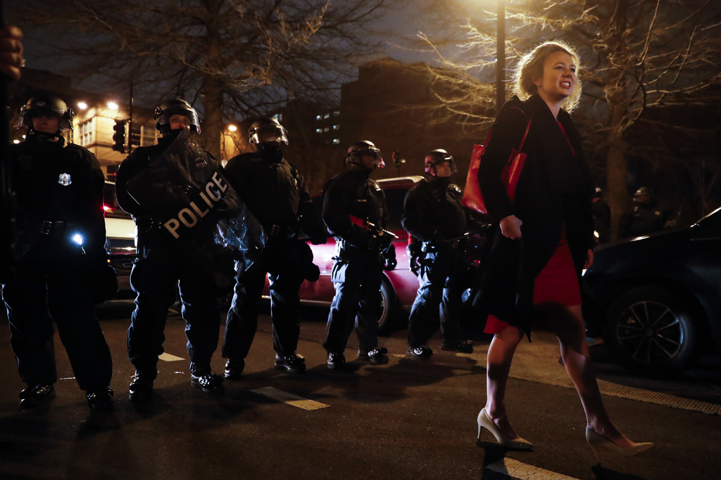 A party-goer is turned away from walking down the street by a line of riot police during a demonstration after the inauguration of Pres...
