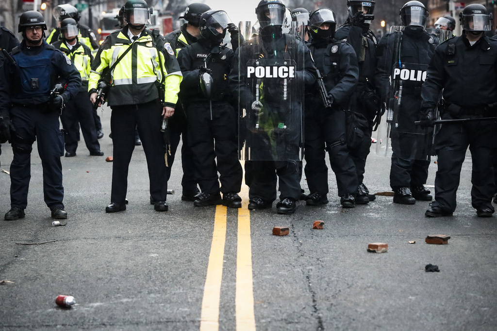 Bricks thrown by protestors rest at the feet of police officers during a demonstration after the inauguration of President Donald Trump...