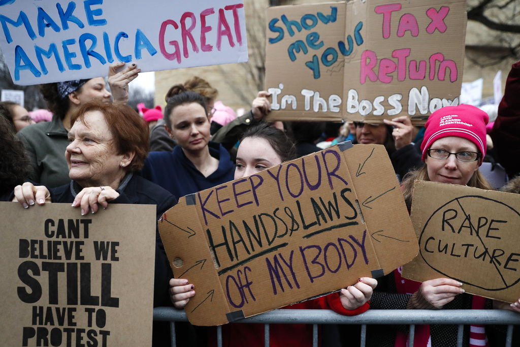 Lily Donahue of Wappingers Falls, N.Y., center, holds a sign along the barricades at the Women's March on Washington during the first f...