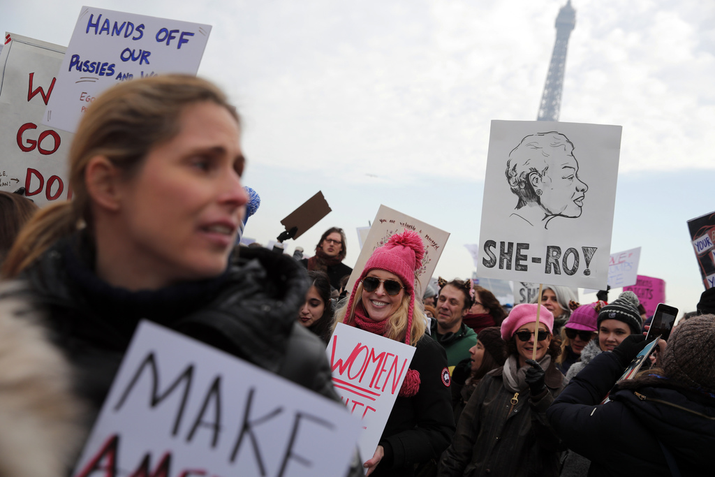 Protesters carrying banners and placards take part in a Women's March next to the Eiffel Tower, in Paris, France, Saturday, Jan. 21, 20...