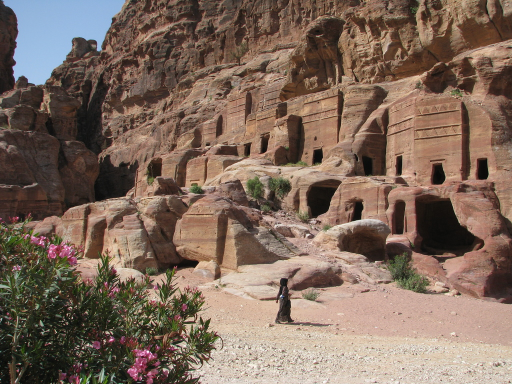 This April 23, 2016 photo shows a woman walking past burial buildings carved out of red canyons in Petra, an ancient city filled with a...