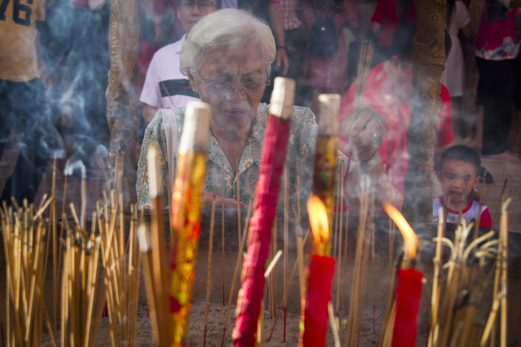 In this Saturday, Jan. 28, 2017 photo, a Malaysian ethnic Chinese woman places joss sticks in the cauldron on the first day of Chinese ...
