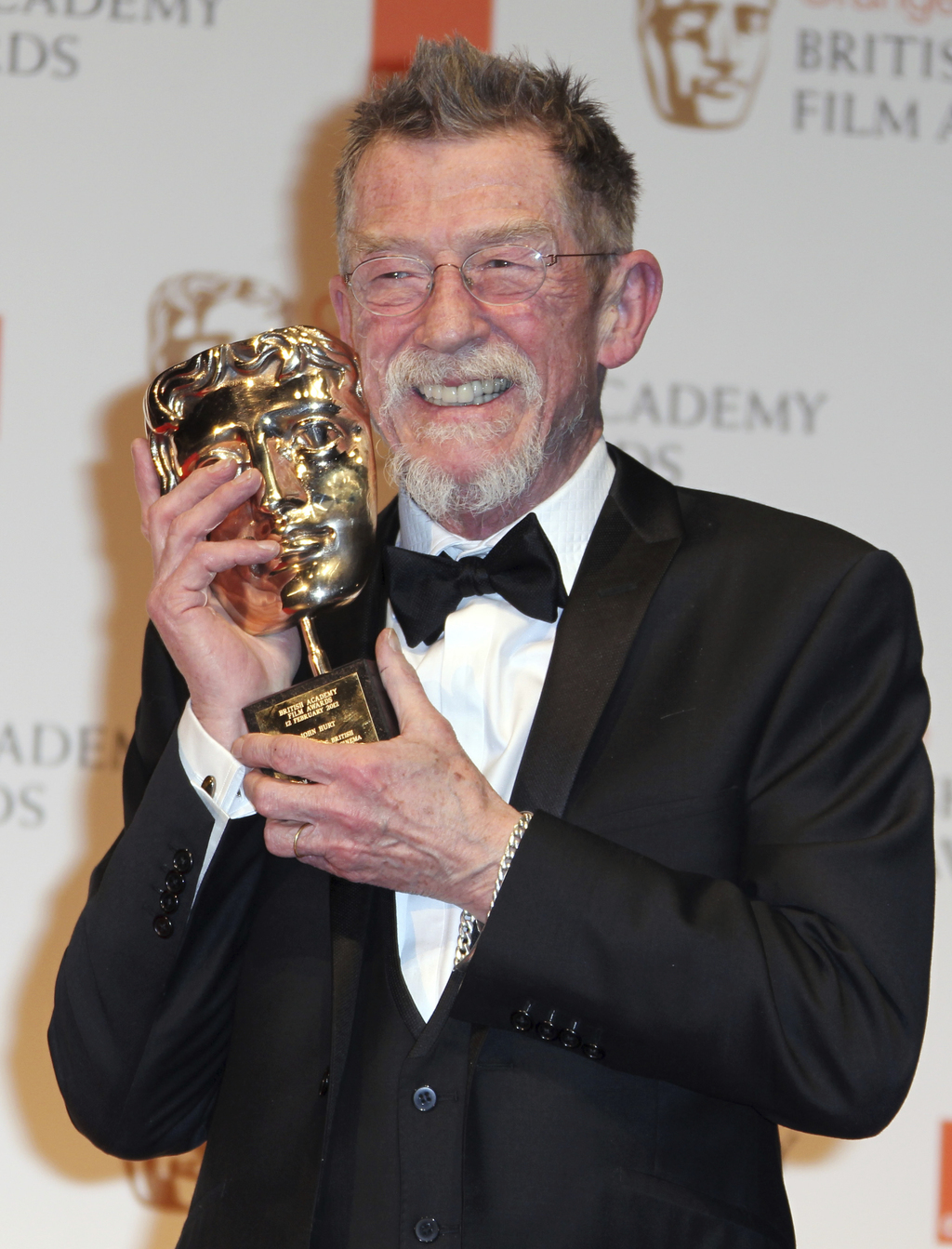 """File - This Feb. 12, 2012, file photo shows actor Sir John Hurt posing with his award for """"Outstanding Contribution to Cinema"""" backstag..."""