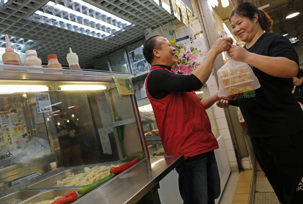 In this Monday, Jan. 23, 2017 photo, chicken feet snacks shop owner Leung Kin-kung, left, hands chicken feet takeaway to a customer in ...