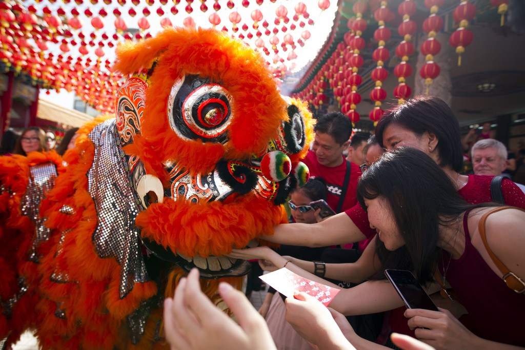 Temple visitors give red packets to the lion dance troupe during the lion dance performance on the first day of Chinese Lunar New Year ...