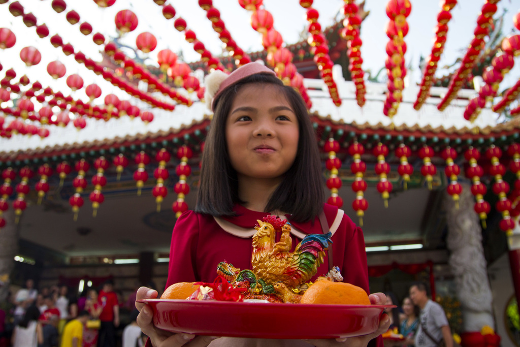 A Malaysian ethnic Chinese girl holds offerings on the first day of Lunar New Year celebrations at a temple in Kuala Lumpur, Malaysia, ...