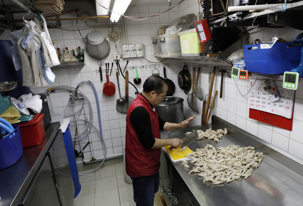 In this Monday, Jan. 23, 2017 photo, chicken feet snacks shop owner Leung Kin-kung chops off chicken feets in Hong Kong. Saturday marks...