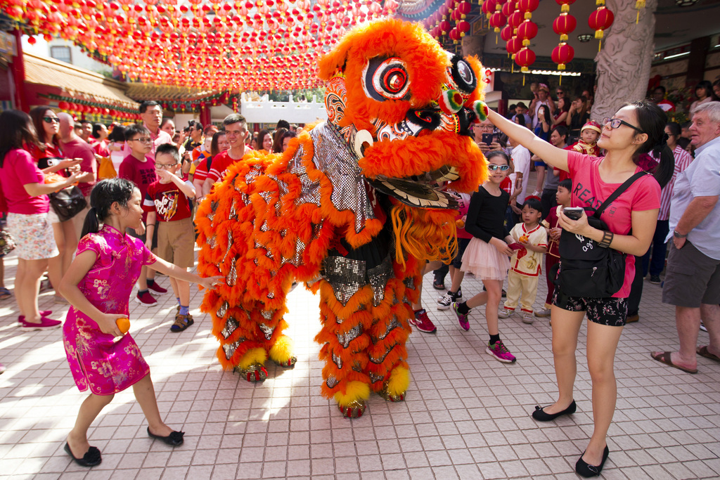 Temple visitors play with the lion dance troupe during the lion dance performance on the first day of Chinese Lunar New Year at a templ...