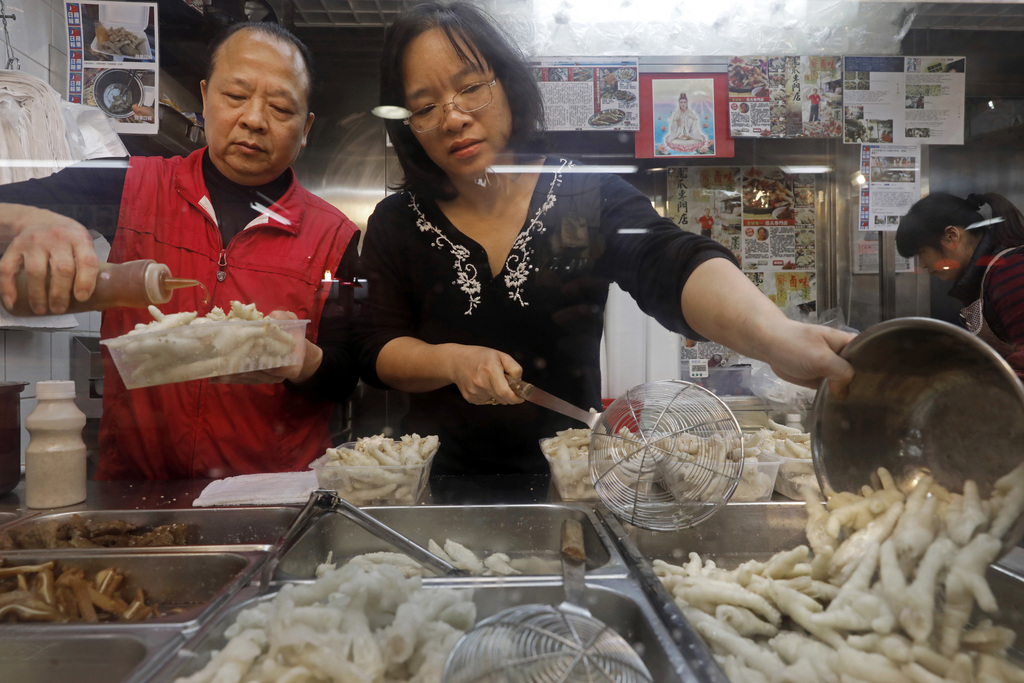 In this Monday, Jan. 23, 2017 photo, chicken feet snacks shop owner Leung Kin-kung, left, and his wife Leung pack chicken feet takeaway...