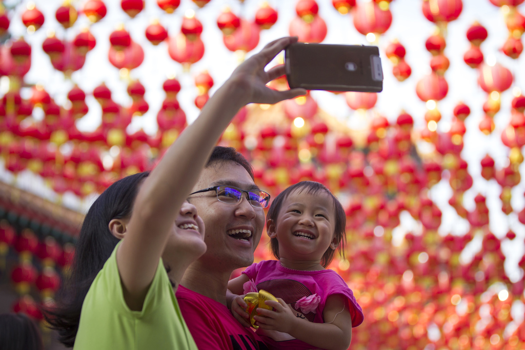 A Malaysian ethnic Chinese family takes a selfie on the first day of Chinese Lunar New Year at a temple in Kuala Lumpur, Malaysia, Satu...