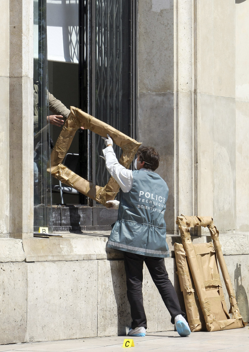 FILE - In this May 20, 2010 file photo,a police officer hands the packed frames of the stolen paintings, to a colleague, from outside t...