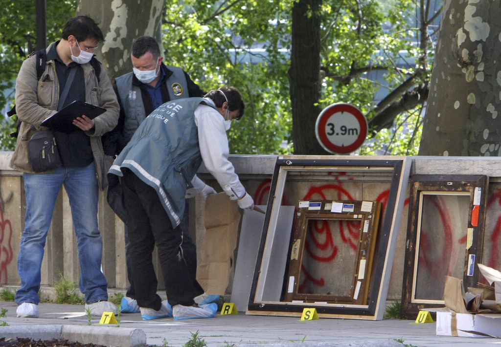 FILE - In this May 20, 2010 file photo, police officers search for clues as they pack up the frames of the stolen paintings outside the...