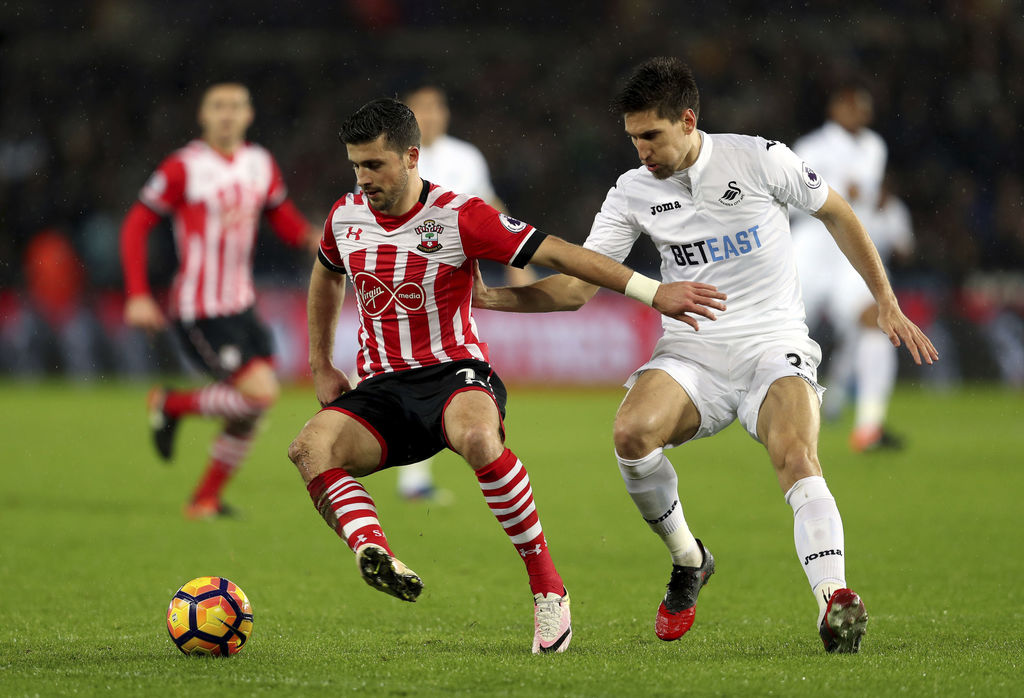 Southampton's Shane Long, left, and Swansea City's Federico Fernandez battle for the ball during their English Premier League soccer ma...