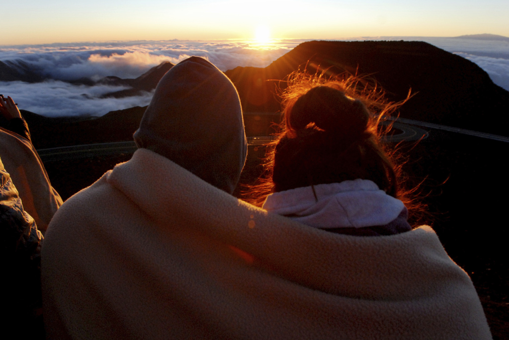 A couple watches as the sun rises in front of the summit of Haleakala volcano in Haleakala National Park on Hawaii's island of Maui, Su...