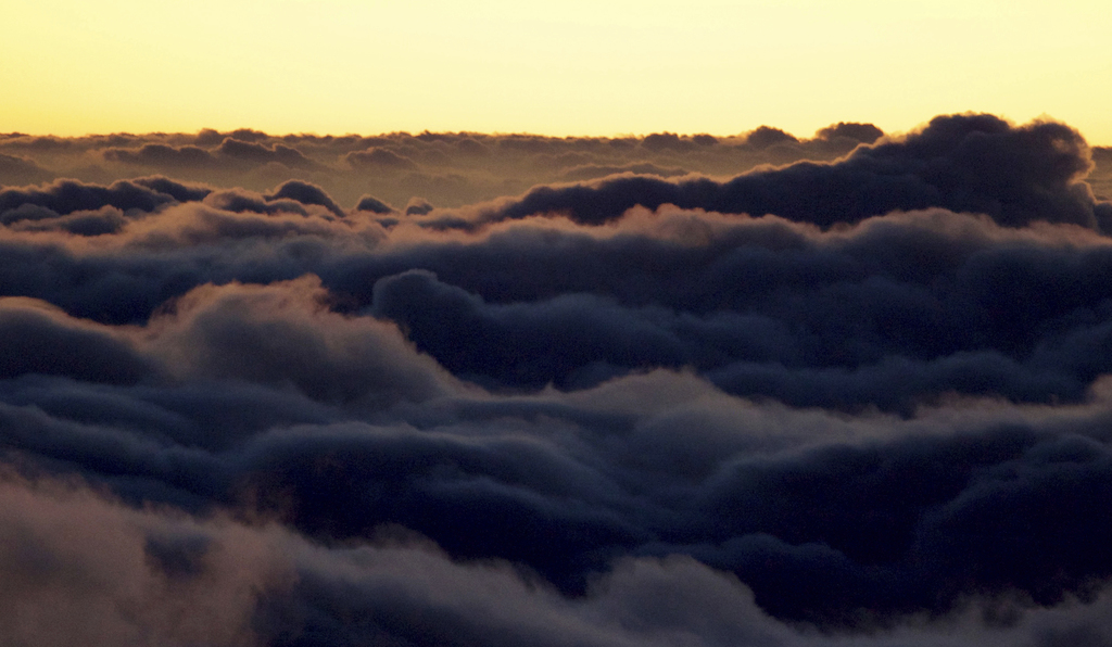 Light reflects off the clouds shortly after sunrise in front of the summit of Haleakala volcano in Haleakala National Park on Hawaii's ...