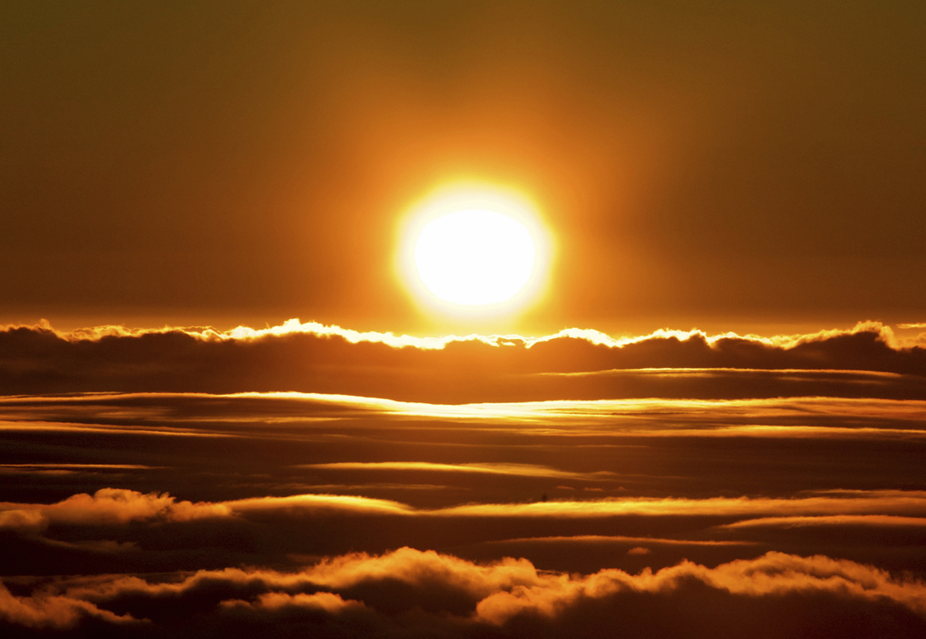 The sun rises over the clouds in front of the summit of Haleakala volcano in Haleakala National Park on Hawaii's island of Maui, Sunday...