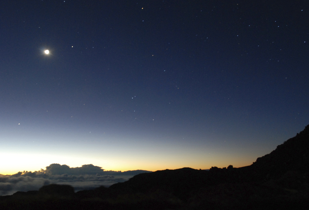 The moon hangs above the horizon as the glow of the sun begins to fill the sky in front of the summit of Haleakala volcano in Haleakala...