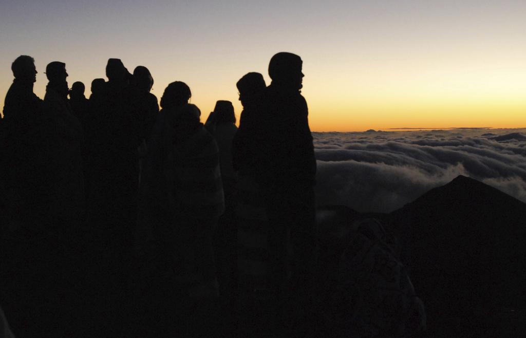 People gather ahead of the sunrise on the summit of Haleakala volcano in Haleakala National Park on Hawaii's island of Maui, Sunday, Ja...
