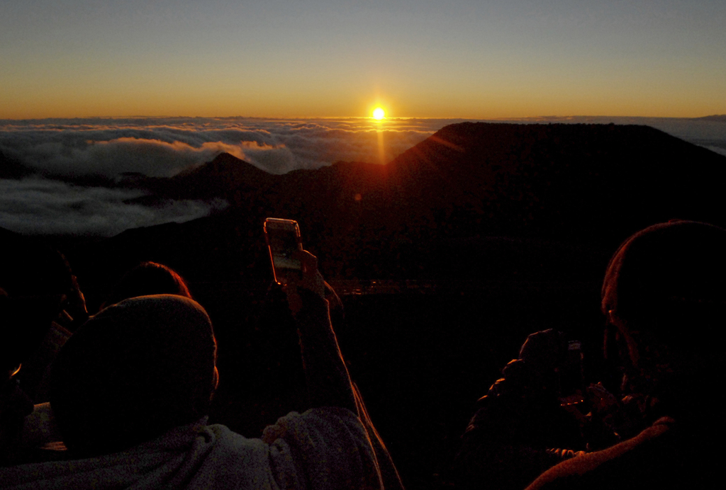 People watch as the sun rises in front of the summit of Haleakala volcano in Haleakala National Park on Hawaii's island of Maui, Sunday...