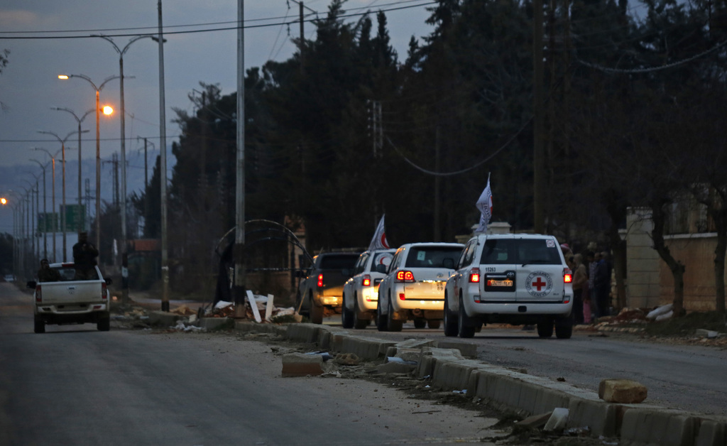 FILE - In this Monday, Jan. 11, 2016 file photo, a convoy of cars loaded with food and other supplies heads toward the besieged town of...