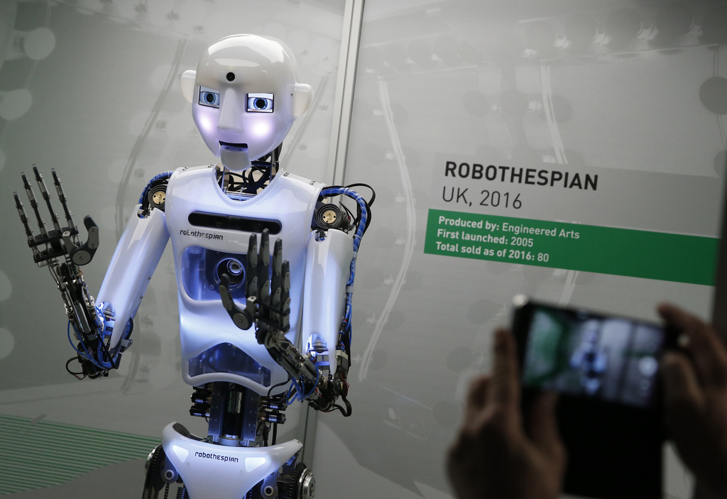 A member of the media takes a smart phone picture of RpboThespian a British built life size robot, during a press preview for the Robot...