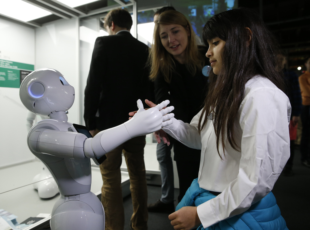 Charllotte Abbot shakes hands with Pepper an interactive French-Japanese robot, during a press preview for the Robots exhibition held a...