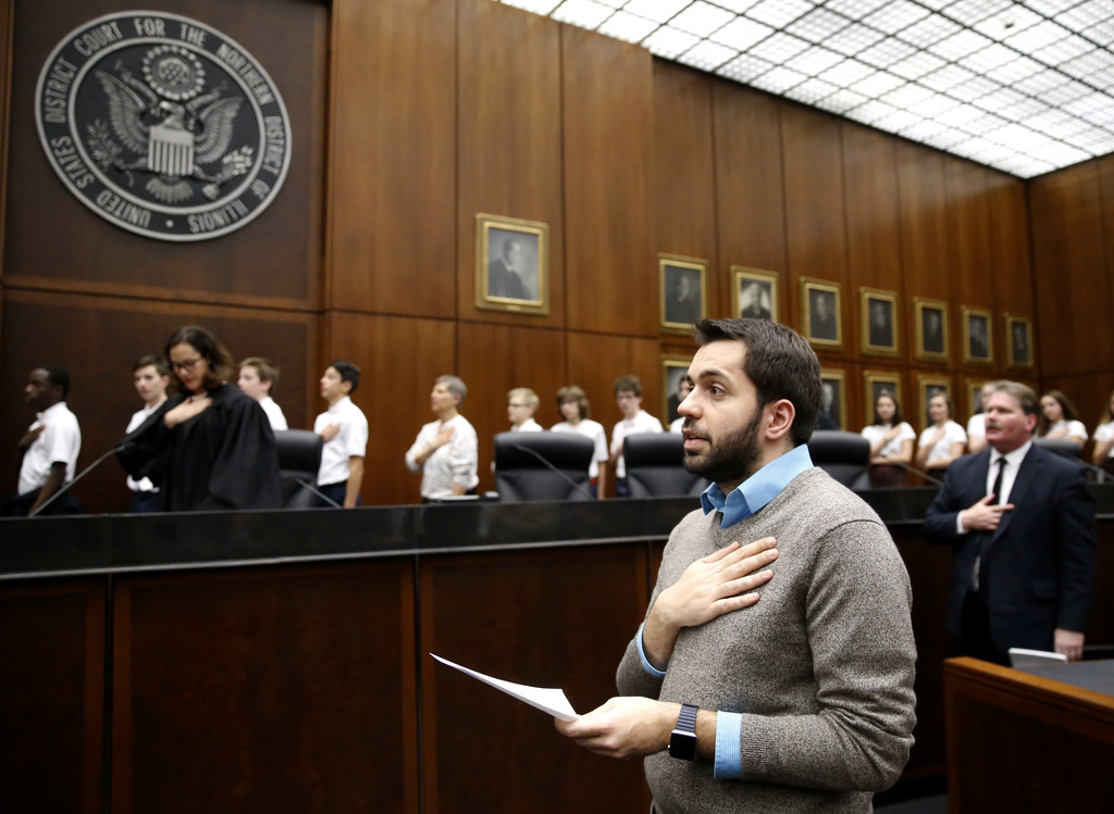 Rohi Atassi, right, from Syria, leads new US citizens in the Pledge of Allegiance after Atassi and 116 others from 37 countries took th...