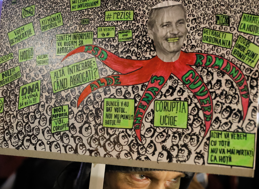 A anti-government protester holds a poster depicting the leader of the ruling Social Democratic party Liviu Dragnea in Bucharest, Roman...