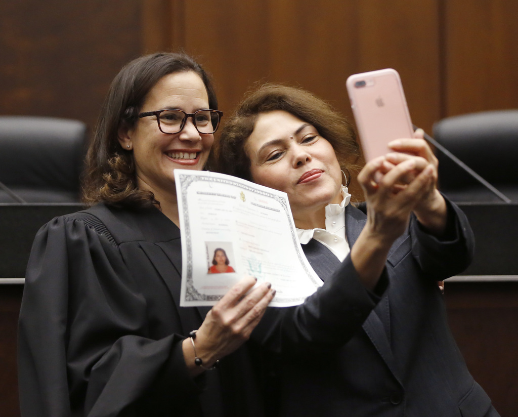 Mirna Araceli Contreras, right, from Honduras, takes a selfie with U.S. District Judge Sara Ellis, in the Northern District of Illinois...