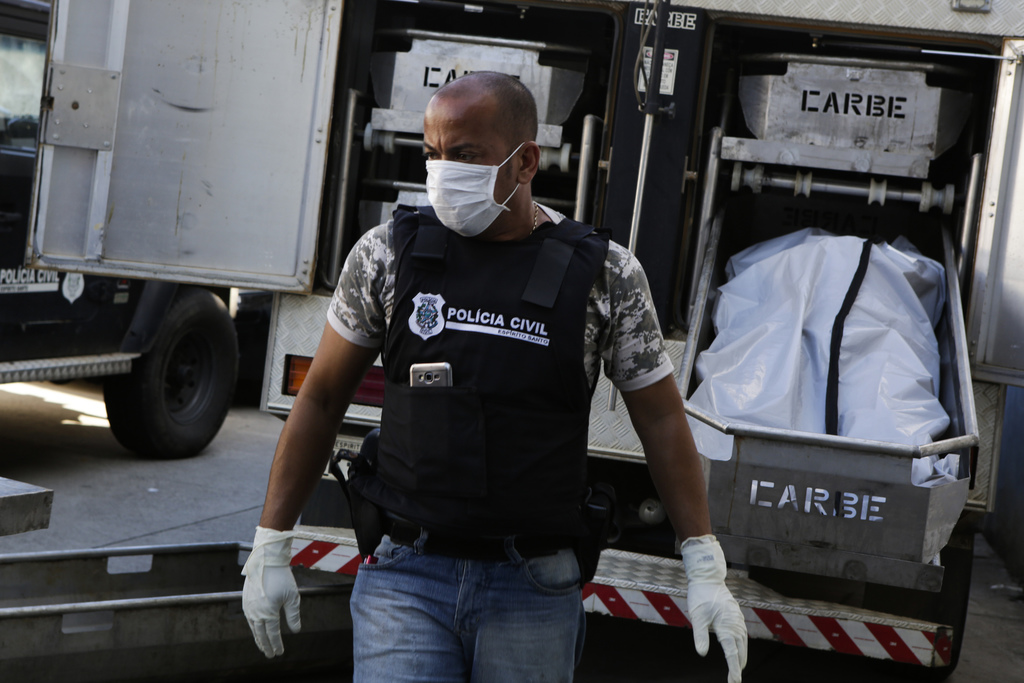 A civil police officer stands next to bodies placed in a coroners truck at the Medical Legal Institute in Vitoria, Espirito Santo state...