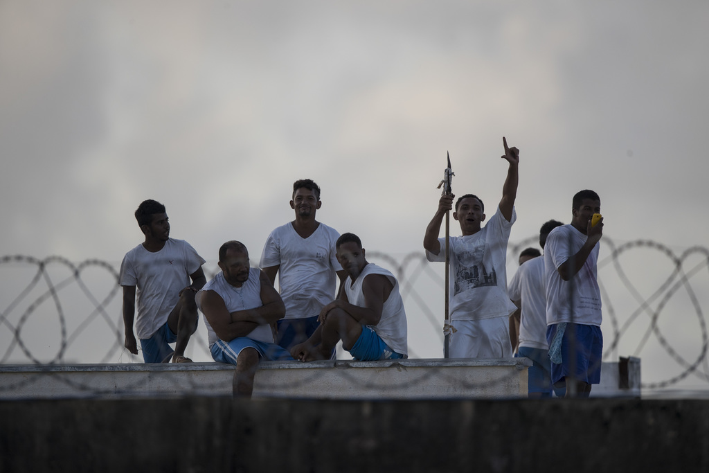 This Jan. 23, 2017 photo shows inmates, one holding a makeshift spear and another using a cell phone, on the roof of Alcacuz prison in ...