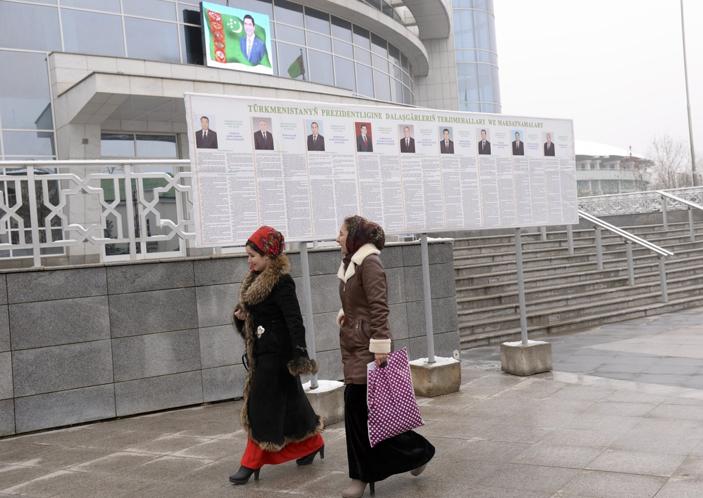 Turkmen women walk passed election posters of President Gurbanguly Berdymukhamedov, top, and other presidential candidates in Ashgabat,...