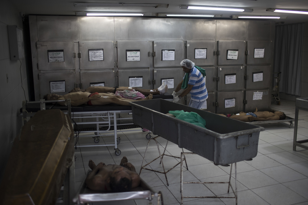 EDS NOTE GRAPHIC CONTENT - In this Jan. 22, 2017 photo, the body of six male homicide victims lay inside a morgue in Natal, Brazil. Mor...