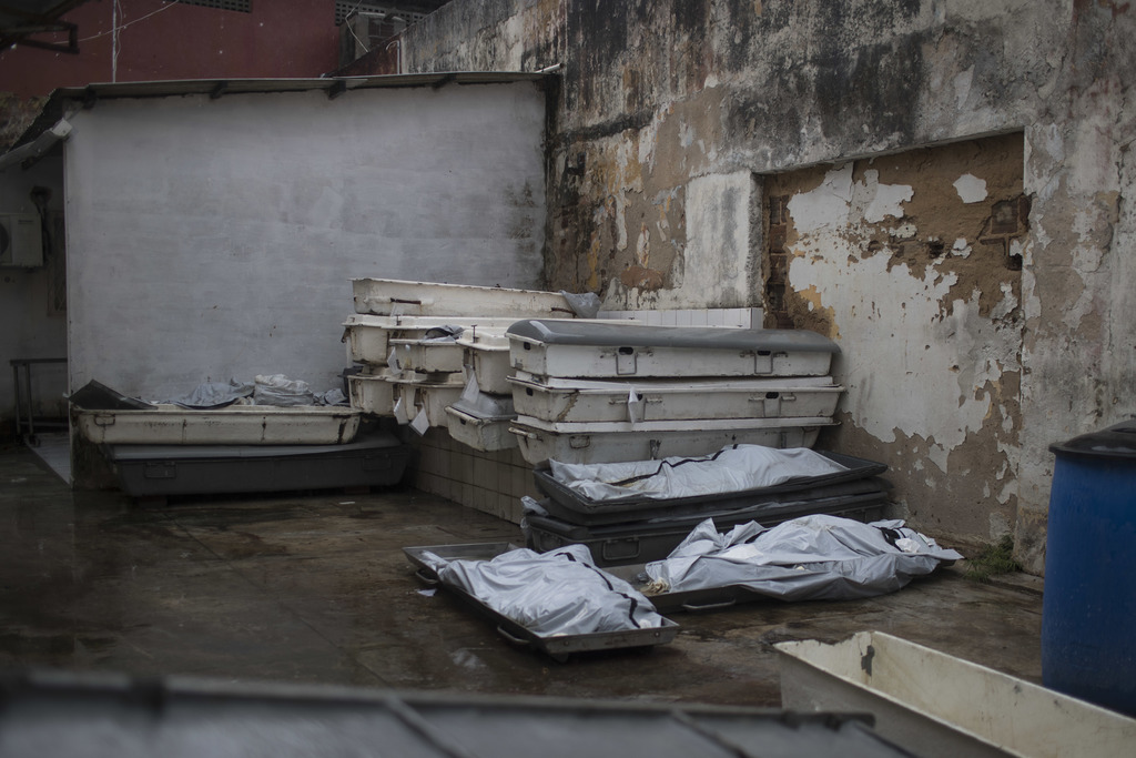 In this Jan. 22, 2017 photo, the bodies of three inmates who were killed in the Alcacuz prison massacre lay outside the morgue in Natal...