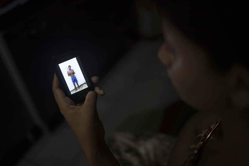 In this Jan. 23, 2017 photo, Sandriely Costa shows a photo, taken inside Alcacuz prison, of her partner Felipe de Oliveira who was kill...