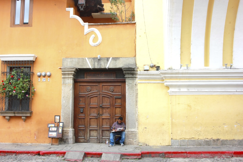 In this photograph taken Dec. 14, 2016, a painter works underneath the Santa Catalina arch in Antigua Guatemala, Guatemala. Established...