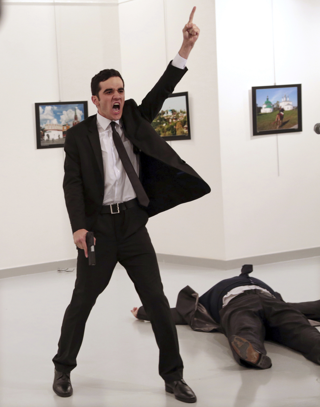 FILE - In this Monday, Dec. 19, 2016 file photo Mevlut Mert Altintas shouts after shooting Andrei Karlov, right, the Russian ambassador...